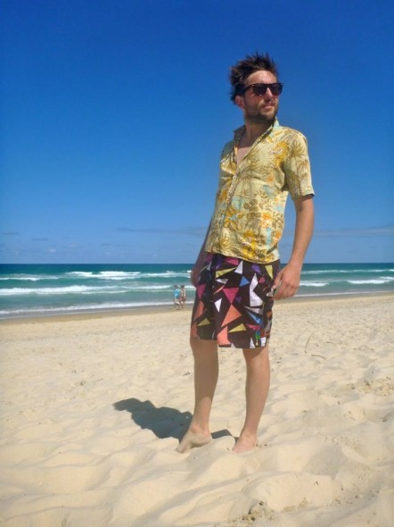 Hamish posing on the Broadbeach beach on the Gold Coast in Australia in the sunshine by the sea in colourful clothes.