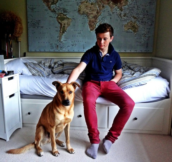 Hamish sitting on bed in his room with Bow Wow dog, Dundee Scotland