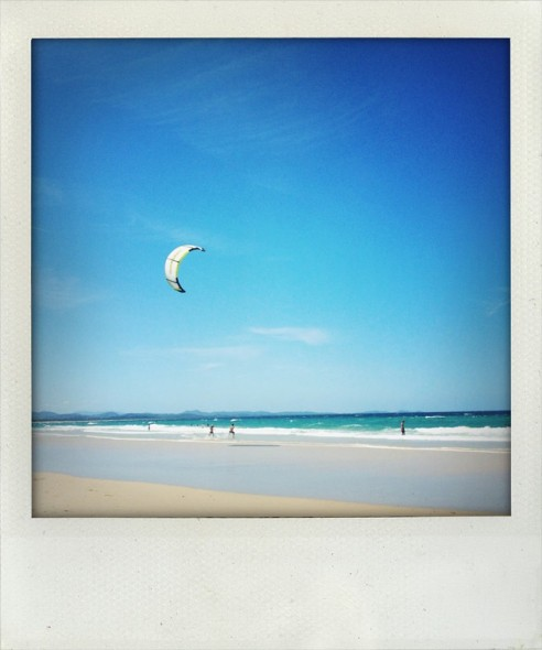 Kite surfer on the beach at Byron Bay in New South Wales in Australia looking out to sea. Taken by Miriam McWilliam.