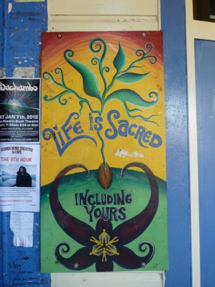 Life is sacred including yours painting in the street in Nimbin in New South Wales in Autralia.