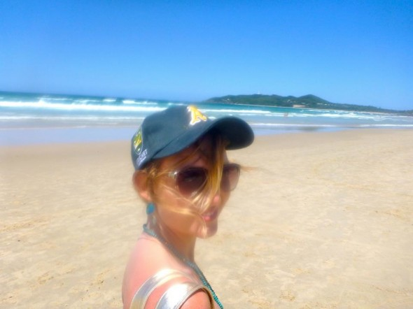 Lucie walking along the beach at Byron Bay in New South Wales in Australia wearing an Australian cricket baseball cap.