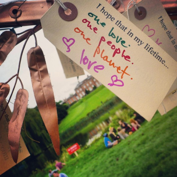 Band4Hope tag hanging from the Ttree4Hope at Shambala Festival reads 'I hope that in my lifetime... one love, one people, one planet. Love.' overlooking the lake and mansion