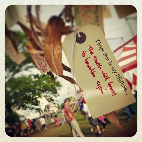 Band4Hope tag tied to the Tree4Hope reads 'I hope that in my lifetime... the Earth will learn to breathe again' at Shambala Festival