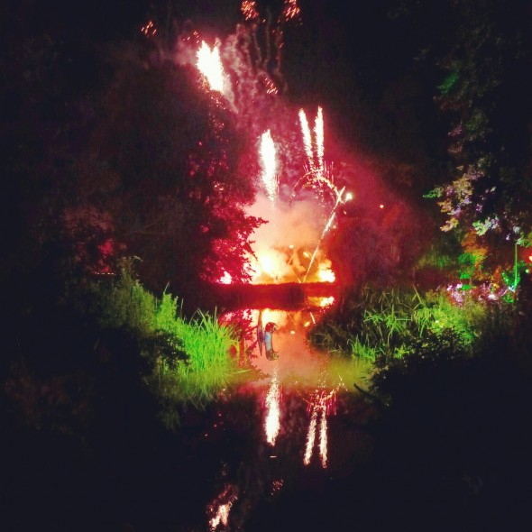 Fireworks over the water with a dragon statue at night at Shambala Festival 2012
