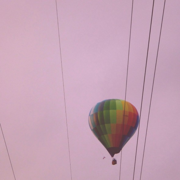 Hot air balloon floating through the pink sky overhead at In the Woods Festival
