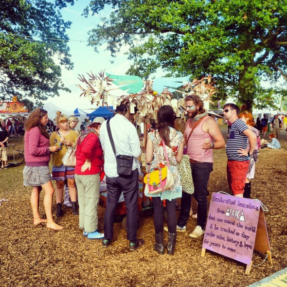 Lachlan McWilliam with a crowd of people around the Band4Hope Tree4Hope at Shambala Festival 2012