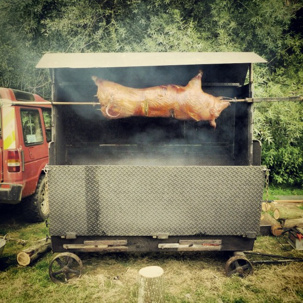 Pig roasting on a spit at In the Woods Festival