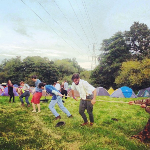 Playing tug of war at In the Woods Festival by the campsite