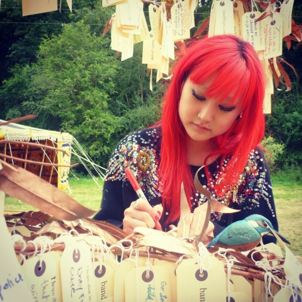 Red haired girl writing her hope for the Band4Hope Tree4Hope at In The Woods festival