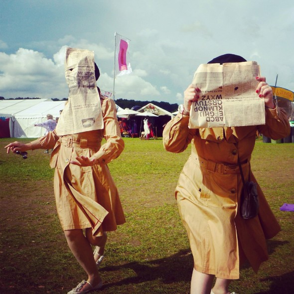 Two ladies dressed as spies wearing macs and with newspaper with eye holes for disguise at Shambala Festival 2012