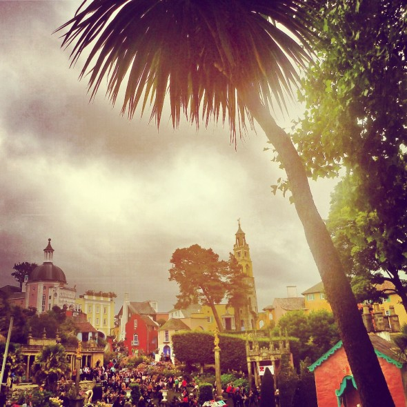 View of the central piazza with festival goers and palm trees at Festival Number 6 in Portmeirion Wales